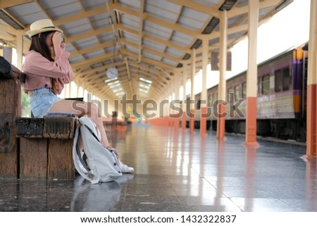 woman traveler holding camera taking photo at train station. travel trip journey concept