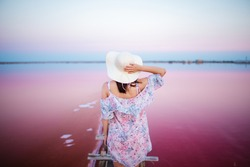 woman traveler holding hat and looking at amazing pink salt lake and pink sky. wanderlust travel concept, copy space for text