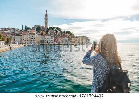 Photo of woman traveler looking at rovinj city from the harbour taking picture on the phone