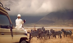 Woman traveler on safari-tour in Africa, traveling by car in Tanzania, watching wild animals and birds in the National park Ngorongoro.