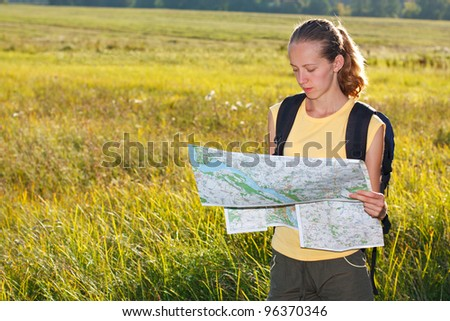Woman traveler read the map among the green summer's nature