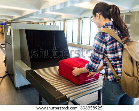 woman traveler selective focus Baggage X-ray machine try to detection metal prevention bad terrorist to attack airplane at the airport before take off.