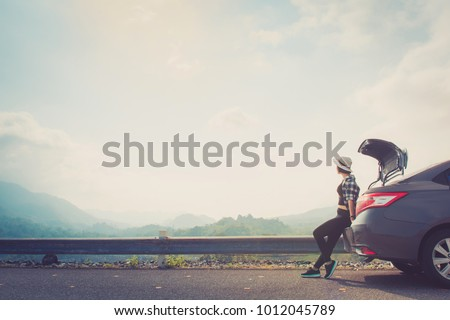 Woman traveler sitting on  car with mountain background iwarm retro tone,copy space.