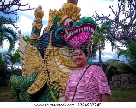 Woman Traveler Stand Beside Big Dragon Statue In The Garden Yard Of Buddhist Monastery, North Bali, Indonesia