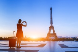 Woman traveler taking a photo of Eiffel Tower from Trocadero with her smartphone during a weekend trip to Paris, France