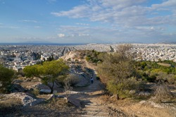 Woman traveler walking by trail on the hill of Philopappos in Athens, Greece.