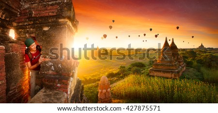 Woman traveler with a backpack explores the ancient temple on a background of beautiful sunrise with balloons. Bagan, Myanmar.