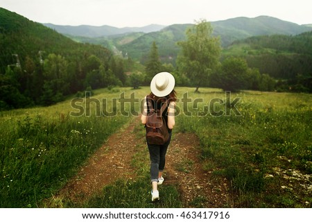 woman traveler with backpack and  hat walking in amazing mountains and forest, wanderlust travel concept, space for text, atmospheric moment. earth day #463417916