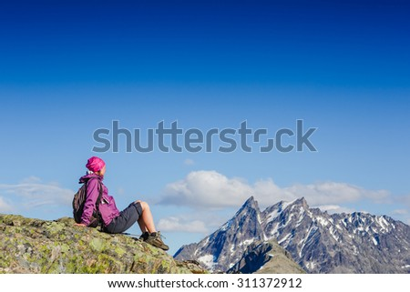 Woman Traveler with Backpack hiking in Mountains with beautiful summer landscape