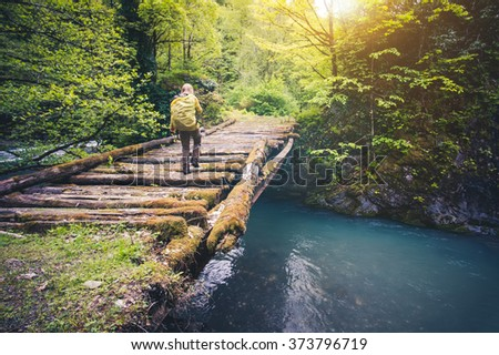 Woman Traveler with backpack hiking on bridge over river Travel Lifestyle concept forest on background Summer journey vacations outdoor