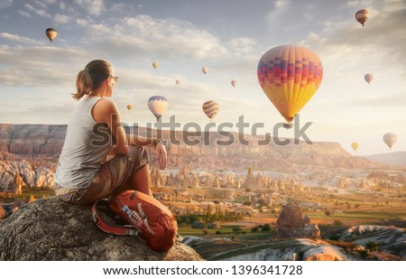 woman traveler with red backpack watching the hot air balloons at the hill of Goreme, Cappadocia, Turkey.