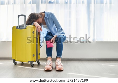 Woman traveler with yellow suitcase affected by flight delay and cancelled travel and vacation holiday. Travel ban and traveling problems