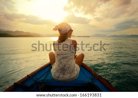 Shutterstock Woman traveling by boat at sunset among the islands.