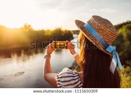 Woman traveling, making photo of beautiful river and mountains nature landscape on smart phone. Traveler girl using smartphone walking outdoor in park, taking mobile picture of sunset forest.