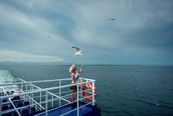 Woman traveling on ferryboat and feeding seagulls flying over the boat from deck, board.