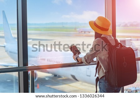 woman traveller holding passport waiting in transit area of airport, stand by for the next schedule traveling, late delay of the arrival departure, missing checking in the boarding pass