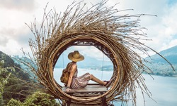 Woman traveller with hat and backpack looking the beautiful landscape of Bali, Indonesia -Wanderlust and lifestyle concept.
