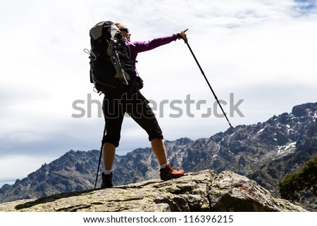 Woman trekker hiking with backpack in mountains, sunset silhouette, trekking in Corsica France. Reaching mountain top, motivational and inspirational concept