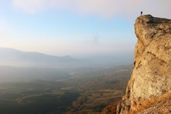 Woman trekker stands on edge of the cliff looking over misty valley
