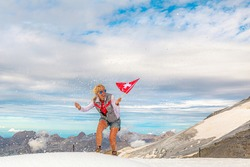 Woman trekking in the snow storm with a Swiss flag. Top of Titlis glacier in the Uri Alps at 3028 meters. Cantons of Obwalden and Bern, Switzerland, Europe. Summer season.