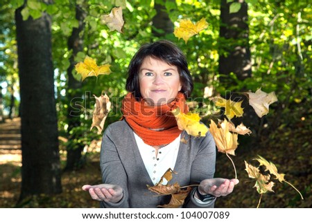 Woman tries to catch falling leaves