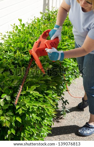 Woman trimming bushes in her backyard using an electrical hedge trimmer.