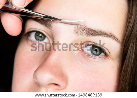 Woman trimming eyebrows with scissors. Eyebrow correction.