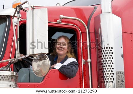 Woman truck driver leaning out the drivers side window. - stock photo