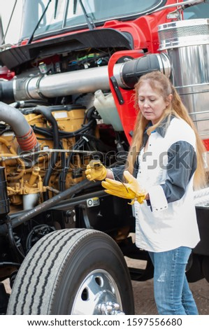 Woman truck driver standing on the wheel while checking fluid levels during a pre-trip inspection of her big rig. Imagine de stoc ©