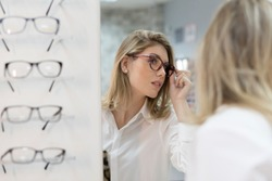 Woman trying on glasses in optical store