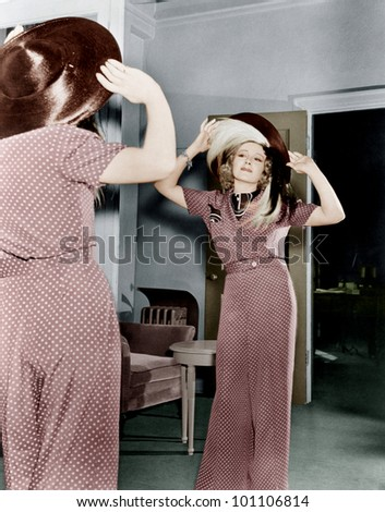 Woman trying on hat - stock photo