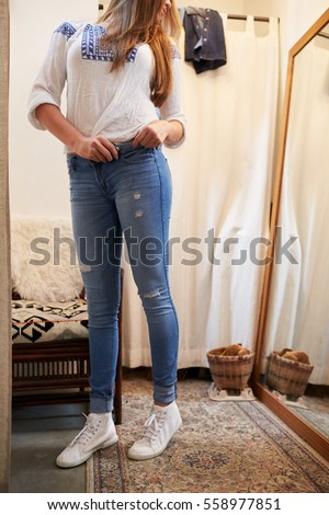 Woman trying on jeans in a changing room looking in mirror