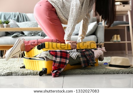 Woman trying to close suitcase with a lot of things. Travel concept #1332027083