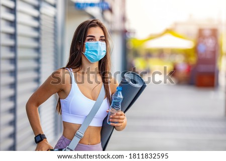 Woman trying to do sport during coronavirus crises despairing of the world. Portrait of a woman exercising wearing a facemask and holding a yoga mat - COVID-19 pandemic lifestyle concepts