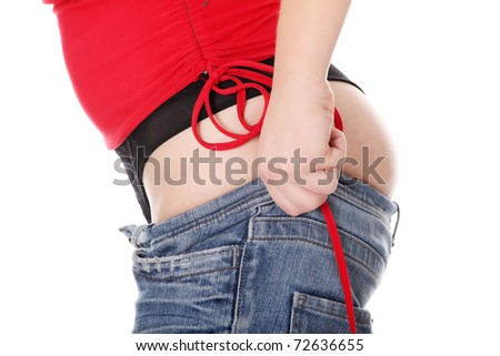 Woman trying to get in to old jeans. Isolated on white