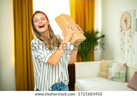 woman trying to guess what is inside the new parcel that si recive, doing shopping online and reciving the products at home