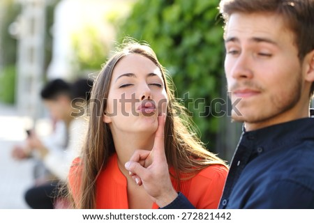 Woman trying to kiss a man and he is rejecting her outdoor in a park