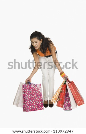 Woman trying to lift shopping bags