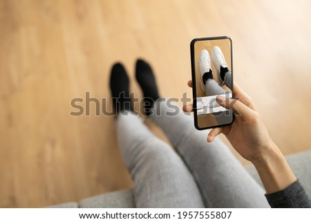 Woman Trying Virtual Sneakers In Shop Or Store AR App Foto stock ©