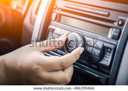 woman turning button of radio in car - Shutterstock ID 486390466