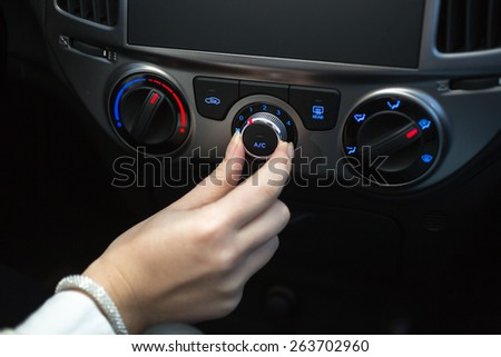 Woman turning on car air conditioning system #263702960