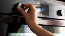 Woman twisting the handle of a modern oven. Concept. Details of cooking at the kitchen, adjusting temperature of a stove.
