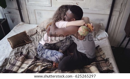 Woman twists the globe, man picks the location to traveling. Multiracial couple in pajamas rejoice, hug and kiss. #625265297