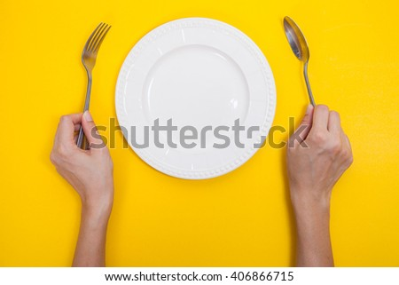woman two hands hold a spoon and fork and white dish on yellow background