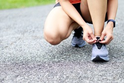 woman tying shoe laces. A female runner is lacing her shoes to prepare for her run.