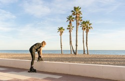 Woman tying the laces of roller skates before training outdoors.Active sport fitness lifestyle concept, on beach with palm trees background with copy space.