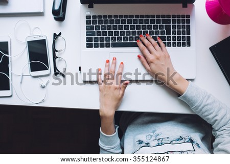 Woman Typing on Her White Laptop Computer At Working Desk.