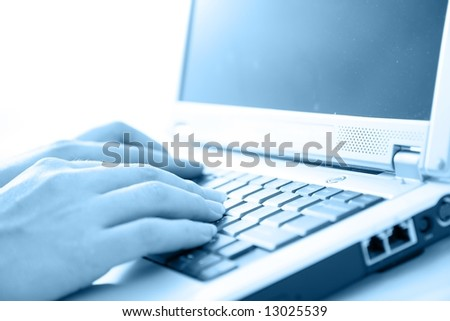 Woman typing on laptop.  High key, selective focus
