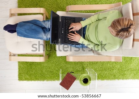 Woman typing on laptop keyboard sitting in armchair with legs crossed on footboard in high angle view.