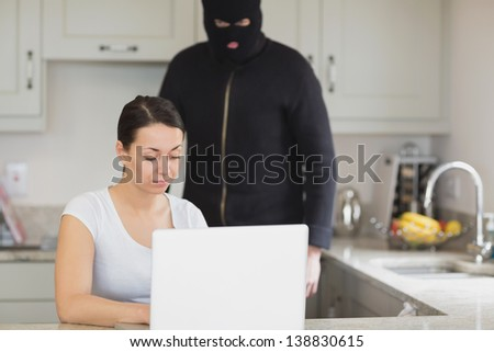 Woman typing on the laptop while burglar looking at it in kitchen